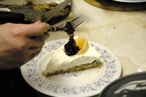 A piece of cheesecake on a plate, with an orange slice on it, while I am adding a dollop of cranberry sauce to the top