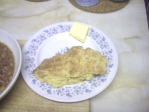 A piece of flattish bread, with a pat of butter beside it on the plate.
