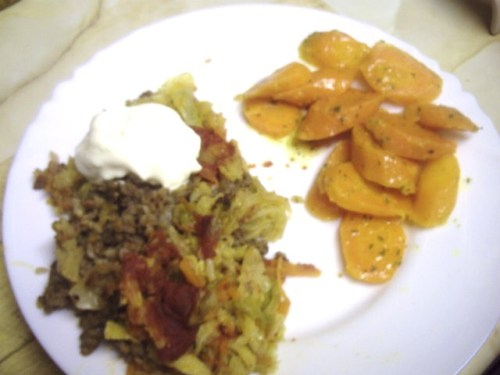 A plate with cabbage roll casserole with a dollop of sour cream on top, and sliced carrots