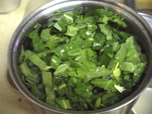 A pot of water with sliced greens in there to wash