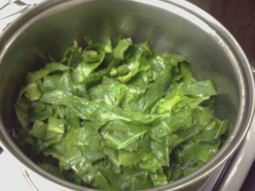 A pot of slightly wilted sliced greens, just after the water went in