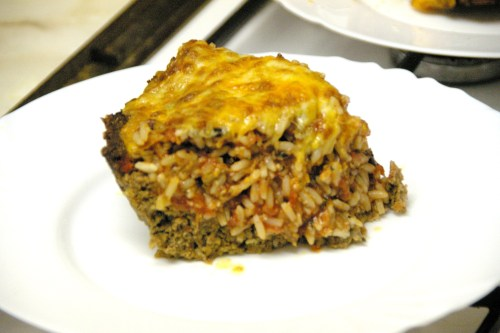 A slice of cheesy meat-and-rice pie on a plate
